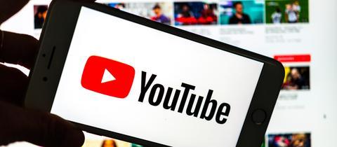 Youtube-Logo auf einem Smartphone.  Im Hintergrund ist auf einem Bildschirm die YouTube Homepage zu sehen.