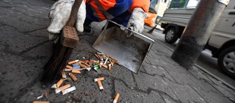 Ein Müllarbeiter entsorgt Zigarettenstummel auf der Straße