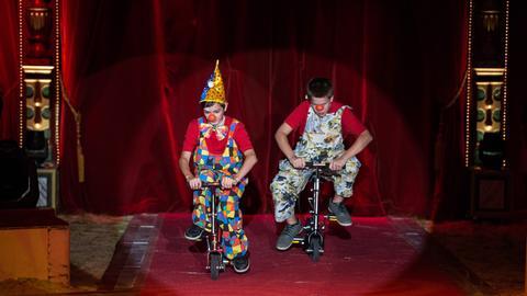 Zwei junge Artisten als Clowns verkleidet üben für den gemeinsamen Auftritt.