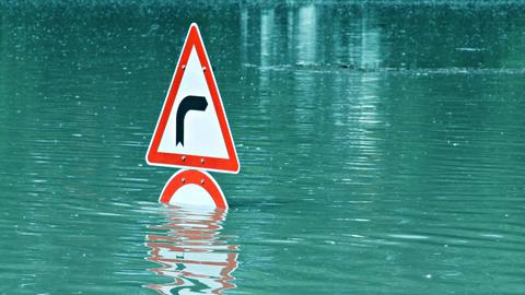 Straßenschild auf überfluteter Straße